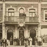 Image: A group of at least 24 men in 1880s attire stand on the street outside a two storey stone terrace building. A further two figures can be seen on the balcony above. The building features decorative window surrounds and extends over a large archway.