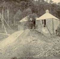 Image: Two single-storey stone buildings stand next to large dirt piles and a wooden tower