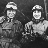 Image: A man and woman wearing First World War-era pilot's clothing and headgear stand in front of a biplane