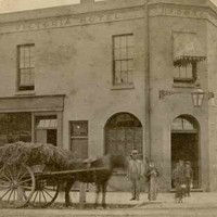 Image: A man, woman and children in 1870s dress stand on the street beside a horse drawn cart laden with straw, outside of a two storey hotel with a corner door, flat roof, arched ground floor windows and awnings over the rectangular second storey windows