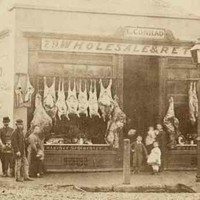 Image: a group of men, women and children in 1860s attire stand outside a single storey building which is operating as a butchers. A range of whole animal carcases are hung outside the store while other cuts of meat can be seen in a window display.