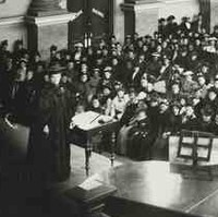 Image: A woman in cap and gown stands on a stage in front of a large audience of women dressed in late Victorian-era attire