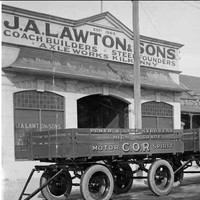 "Image: three four wheeled trailers are parked in a row outside of a single storey building with arched windows and open entranceway. A parapet sign on the building reads: ""J.A. Lawton & Sons. Coach builders, Steelfounders, Axelworks, Kilkenny"""