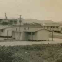 Image: A group of single-storey prefabricated buildings are situated on a remote piece of scrubby land. Low hills are visible in the distant background