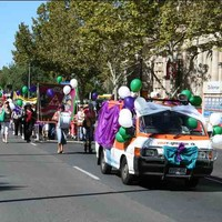 Image: women carrying banners and holding green and purple balloons march down a city street following a van decked out in balloons, bows and swathes of coloured fabric. One of the women near the front is beating a large drum