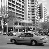 Image: late 1990s and early 2000s cars wait at an intersection of a street lined with skyscrapers