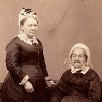 Image: sepia photograph of two women, one seated, one standing, wearing black dresses with white lace collars and white bonnets. The seated woman, the elder of the two, holds a book on her lap.
