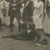 Image: A theatrical still of a group of people looking on with concern as two young women attempt to restrain a man from hitting another man who has fallen to the ground in a fight. In the background is a country homestead