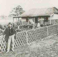 Image: A man in a bowler hat leans against a fence surrounding a garden. A small cottage connected to the garden is in the background