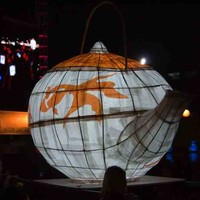Image: A large white and orange paper lantern in the shape of a teapot glows in the dark as it is carried by a group of people in front of a stage lighting rig illuminated in pink and a banner reading moon lantern festival.