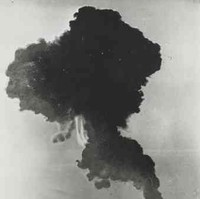Image: A large mushroom cloud dissipates over a vast, flat expanse of land. A line of telephone poles are visible in the foreground