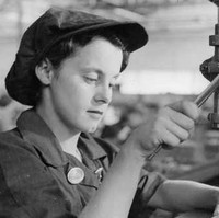 Image: A young woman uses a drill press to manufacture holes in a sheet of metal