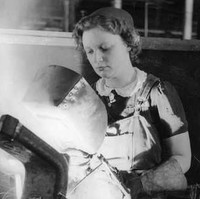 Image: A young woman welds a large metal bracket held in a vise