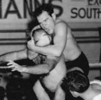 Image: A wrestler jumps on the back of his competitor while another man acting as referee looks on