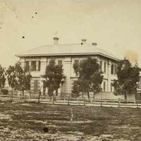 Image: a square two storey stone building with protruding columned portico sits behind a line of trees and a simple wooden fence. The road in front of the fence is extremely muddy.