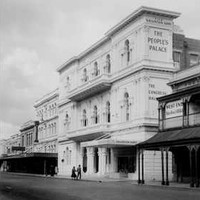 """Image: A three storey building with arched windows, decorative plasterwork and a columned portico. A sign painted on its side reads: """"The People's Palace"""""""
