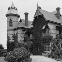 Image: A large, two-storey stone mansion with a cylindrical turret comprising one corner of the structure