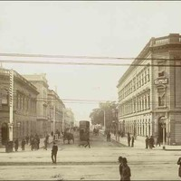Image: a sepia photograph of a busy street, filled with horse drawn vehicles and pedestrians in 1870s attire, and lined with two and three storey stone buildings.