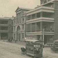 Image: a horse drawn tram travels down a wide dirt city street which is lined with a series of three and four storey buildings, many with balconies and verandahs, including a theatre with a large arched entrance and column decoration on the upper floors.