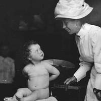 Baby Evangeline Gabriel being being weighed by a nurse 1908
