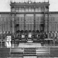 Image: a low stage, with the wall behind covered in decorative wooden panelling, supports rows of chairs, a small table and a lecturn. The stage also has further rows of chairs facing it.