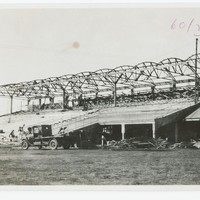 Image: Construction of a grandstand with old vehicle in the foreground.