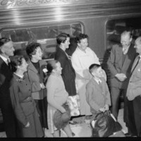 Image: Six people, both adults and children stand in front of a train on a station platform. They are laughing and conversing.
