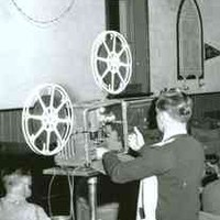 Image: A young man operates a film projector in a large church hall filled with seated people of all ages