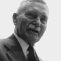 Image: A photographic portrait of a moustachioed middle-aged man wearing a suit