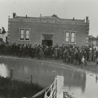 Image: A building with a large group of men gathered around the front.