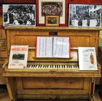 Image: upright piano covered in signatures