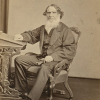 Image: A man wearing a suit sitting in a chair with one hand resting on a small pedastal