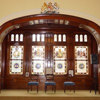 Image: A large alcove containing four intricate stained-glass windows with Australian and British motifs