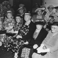 Image: Group of elderly women sitting in a room wearing hats