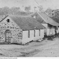 Image: Two gable roof, stone cottages sit adjacent to each other with the hills and gum trees of Lobethal in the background