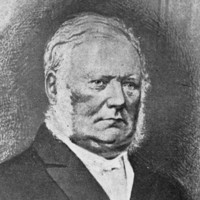 Image: The head and shoulders of a middle-aged man with white hair and mutton-chop sideburns