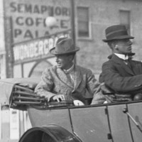 Image: Four men travel in an early twentieth-century car. A couple of buildings are visible in the background, including one with the words 'Semaphore Coffee Palace' painted on its side