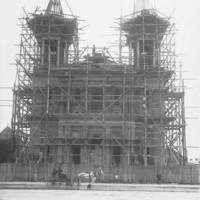 Image: A large stone church with twin spires is under construction and surrounded by scaffolding