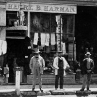 Image: three men stand outside a drapery shop in part of a two storey terrace building. A figurine of a woman holding a trident can be seen above the door to the shop.