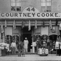 Image: A group of men and children stand outside a two storey terrace building the ground floor of which is serving as a drapery store with fabric sitting in baskets on the street, coats hanging along the storefront and hats in the window.