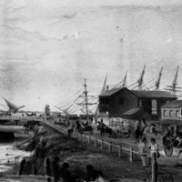 Image: A shallow creek contains two boats, one upturned. A small group of Aboriginal people sit in the foreground. On the right is a busy street with horse drawn wagons taking bales to be loaded onto ships in the background