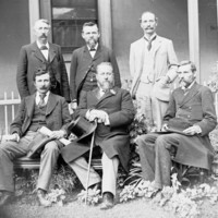 Image: black and white photograph of six men, three seated and three standing in front of a building. Kingston is seated in the front middle and wears a flower in his lapel.