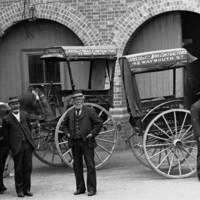 Image: Five men in uniforms stand in front of three horse-drawn carts in a building courtyard. Painted on the side of the carts are the words 'J. Reid & Co. Mail Contractors, 42 Waymouth St.'