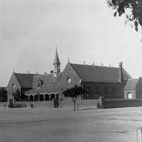 Image: A group of children stand on the street outside a walled symmetrical stone building with a verandah with stone arches, a central spire, and two gable roofed wings with rose windows on the facade and double arched windows along the sides.