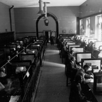 Image: A group of men sit at two rows of tables in a large open room. Each man has telegraph equipment on the table in front of him