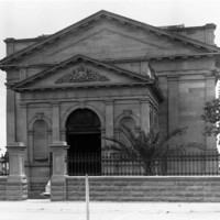 Image: a windowless classical revival style stone building behind a stone and wrought iron wall/fence