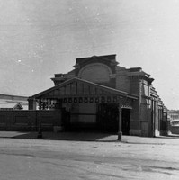 Image: two brick buildings with decorative verandahs which serve as entranceways to a railway station.