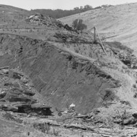 Image: A stone quarry cut into the side of a rolling hill. A wooden derrick is positioned adjacent to the top of the quarry