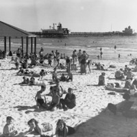 Image: People sunbathing on a beach with a jetty in the background.