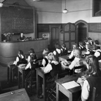 Image: Girls in black pinafores over white blouses sit at wooden desks with open books facing a blackboard. Under the blackboard, behind a large desk on a raised platform sits a woman, their teacher, also with an open book.